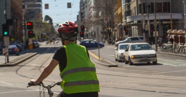 A cyclist in a high-vis vest rides on a street with cars in the background