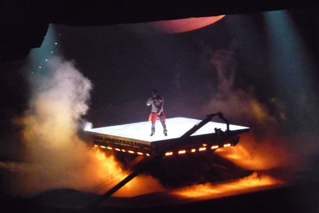 Kanye West stands on elevated platform during Chicago Tour